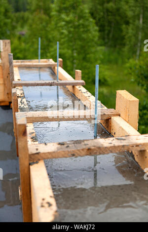 Wooden formwork concrete strip foundation for a new house - Stock Photo