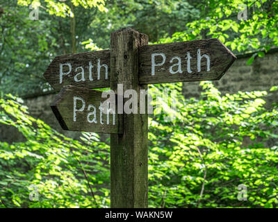 A wooden footpath sign in a forested area of the Scottish Highlands - Stock Photo