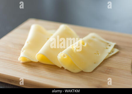 Slices of cheese on wooden background. Holland cheese with holes. - Stock Photo