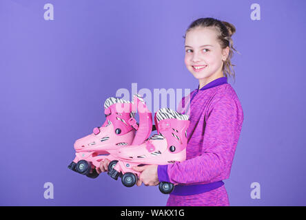 Learning to skate is fun. Cute little skater. Small girl holding pink roller skates. Little child with inline skates. Roller sport. Skates or sports shoes on wheels. Skating on inline roller skates. - Stock Photo