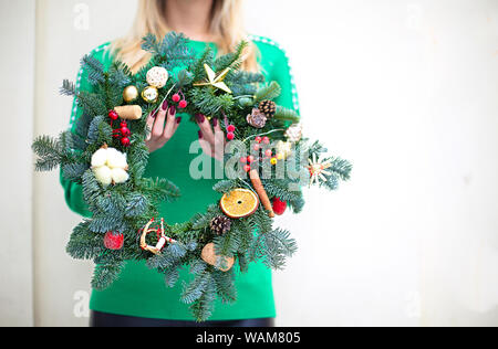Woman holding Christmas wreath maked by herself. Close up - Stock Photo