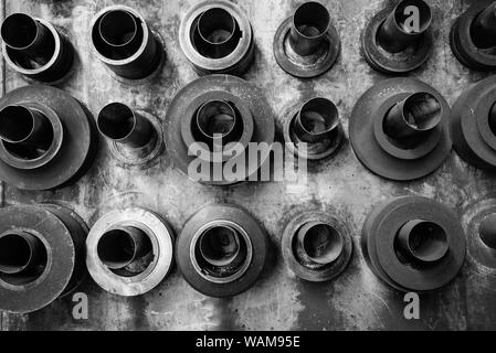 A black and white image of a grimy dirty wall with steel rings and dies mounted on steel pipes in a workshop - Stock Photo
