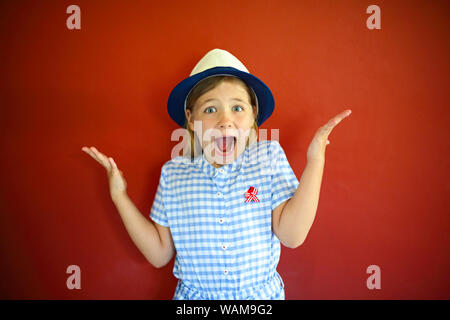 Pretty emothional children wear a hat on a red background. Copy space, daylight - Stock Photo