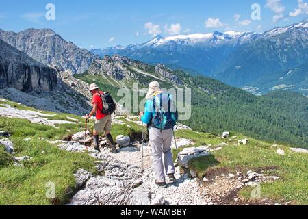 Two hikers hiking in Brenta Dolomites, Italy with rocky landscape in the background