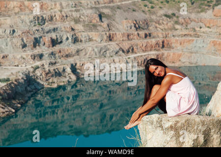 beautiful woman with long hair sitting on a cliff by the lake - Stock Photo