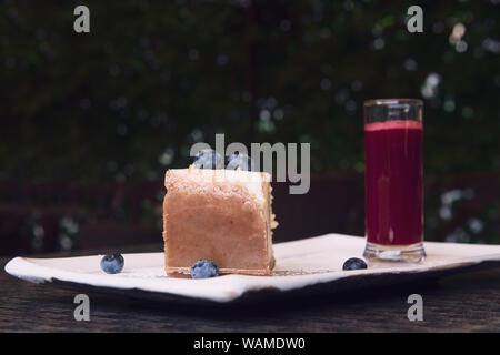 New York cheesecake with blueberries. A slice of a tasty pie with a brown crust. Served with glass of raspberry sauce. Closeup with bokeh and copy spa - Stock Photo