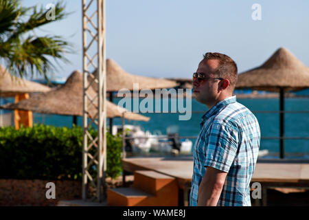 Portrait of tourist and traveler is posing and watching on beautiful beach of hotel resort in Egypt, enjoys in sun and view of sea landscape. - Stock Photo