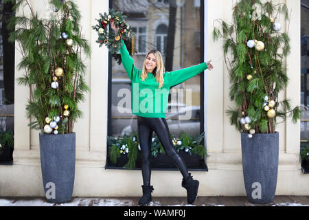 HAppy young girl holding Christmas wreath maked by herself - Stock Photo