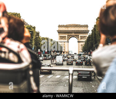 Great view from city tour bus driving through Champs Elysee Avenue on a beautiful sunny day towards Arch of Triumph. Vintage photo - Stock Photo