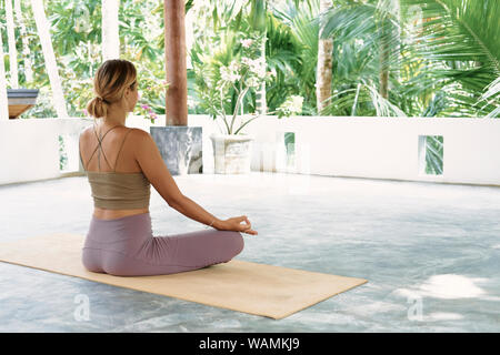 Woman Practicing Advanced Yoga on Organic Mat. Series of Yoga Poses. Tropical background. lifestyle Concept