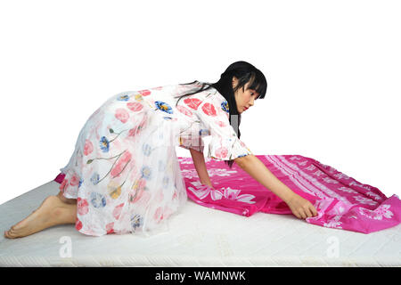 Cute Asian Girl Changing Clean Bed Sheet. isolated on White Background. - Stock Photo