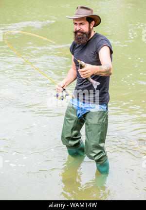 Brutal man wear rubber boots stand in river water. Fisher weekend activity. Fisher with fishing equipment. Fish on hook. Leisure in wild nature. Fun of fishing is catching. Fishing masculine hobby. - Stock Photo