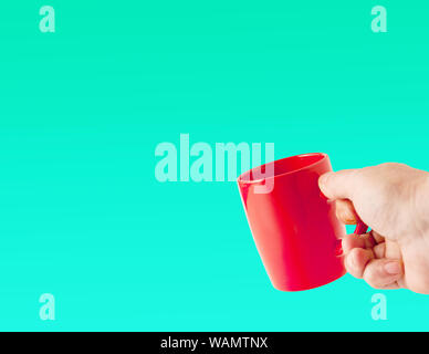 hand holding a red cup on a blue background arrangement on the right - Stock Photo