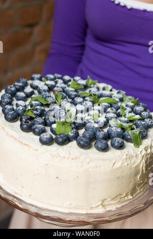 Woman in a lilac shirt holding a homemade white birthday cake with organic blueberries and mint on top. Party dessert. Celebration of birthday. Stylis - Stock Photo