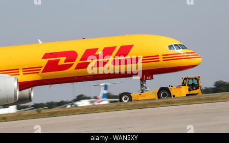 Schkeuditz, Germany. 21st Aug, 2019. A DHL cargo aircraft is towed to an apron position at Leipzig-Halle Airport. Credit: Jan Woitas/dpa-Zentralbild/dpa/Alamy Live News - Stock Photo