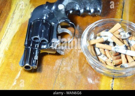 revolver gun and cigarette in glass ashtray on wooden table - Stock Photo