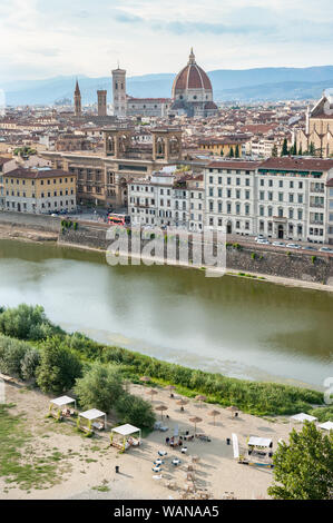 Sunbed and sunshades on the Arno river urban beach. Florence cityscape with Basilica Santa Maria del Fiore, Giotto's tower, National Central Library. - Stock Photo