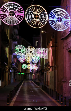 This is a view of a street in Almansa, Spain at night decorated with lights. - Stock Photo