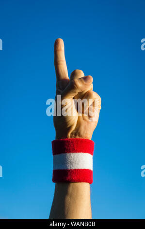 Close-up of hand of number one Japanese athlete wearing red and white Japan colors wristband with finger pointing skyward - Stock Photo