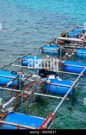 Workers settle and setup the waterworks fountain machine on the surface of the sea. - Stock Photo