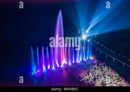 Waterworks at the night on the water surface, decorated and played color by lighting spot light. - Stock Photo