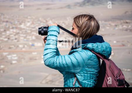 Mongolia Ulgii 2019-05-04 European blonde girl in blue jacket looking through binocular, hiking, climbing, walking. Concept independent traveler on vi - Stock Photo