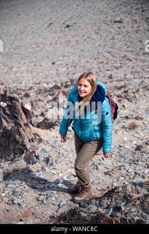Mongolia Ulgii 2019-05-04 European blonde girl in blue jacket hiking, climbing, walking on background mountain, village. Concept lonely traveler, inde - Stock Photo
