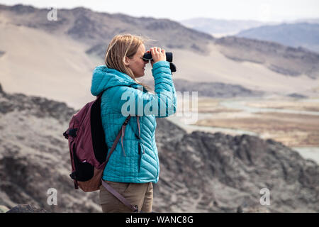 Mongolia Ulgii 2019-05-04 European blonde girl in blue jacket looking through binocular into the distance, bird watching, hiking, climbing, walking. C - Stock Photo