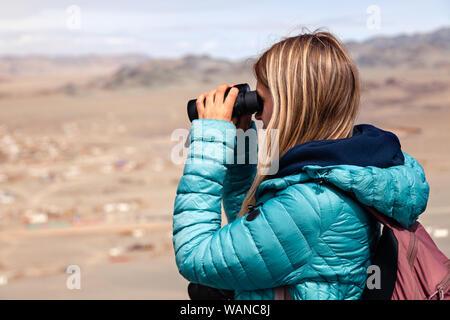 Mongolia Ulgii 2019-05-04 European blonde girl in blue jacket looking through binocular, hiking, climbing, walking on mountain background. Concept lon - Stock Photo