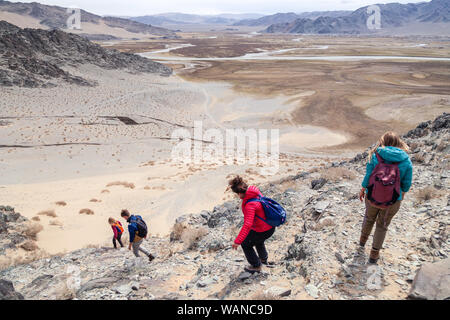 Mongolia Ulgii 2019-05-04 Tourist group go hiking and climbing together with guide, coming down from mountain top. Back view. Concept freedom, backpac - Stock Photo