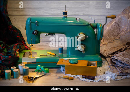 still life with vintage electric sewing machine and a variety of sewing accessories - Stock Photo