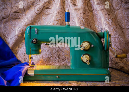 still life with vintage electric sewing machine and and bright blue fabric - Stock Photo