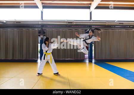 Side view of two young women in white kimonos attacking and fighting. - Stock Photo