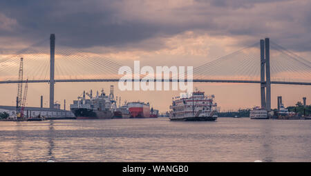 Waterfront of Savannah, Georgia, USA - July 22, 2018: A Riverboat Cruises as it leaves the Port of Savannah in Georgia at sunset - Stock Photo
