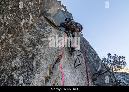 A young woman climber sets out on her first aid climbing lead - Stock Photo
