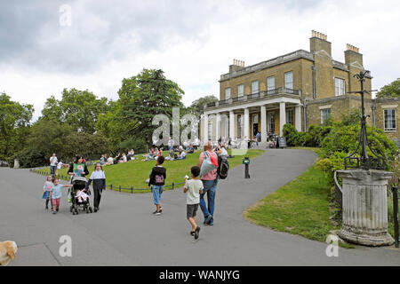 Families strolling along the path outside Clissold House and sitting on the lawn in Clissold Park in summer Stoke Newington London UK  KATHY DEWITT - Stock Photo