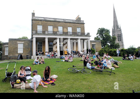 Clissold Park, house, church steeple and people families relaxing outside on the front garden lawn Stoke Newington North London N16 UK  KATHY DEWITT - Stock Photo