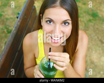 Close up view from above of girl drinking green detox smoothie in the park. - Stock Photo