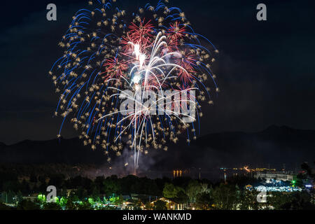 A red, white and blue display of fireworks shoots off above Estes Park on the Fourth of July. - Stock Photo