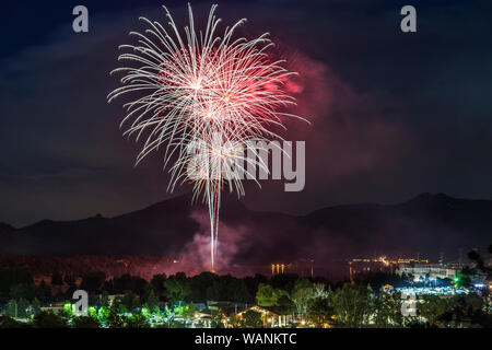 A red and white display of fireworks shoots off above Estes Park on the Fourth of July. - Stock Photo