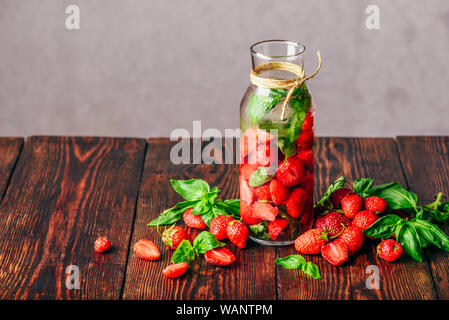 Flavored Water in Bottle with Fresh Strawberry and Basil Leaves. Scattered Ingredients on Wooden Table. Copy Space. - Stock Photo