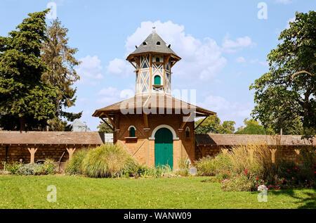 Priory Castle Garden, stone wall, octagonal building, greenspace, flowers, trees, green grass, Europe, Conflans Sainte Honorine; France; summer, horiz - Stock Photo