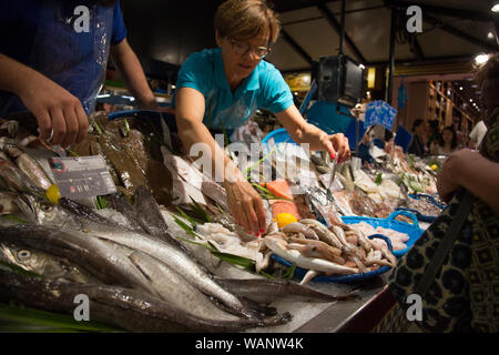 A fishmonger selling fish at a stall in the Marché Victor Hugo covered food market in Toulouse, France - Stock Photo