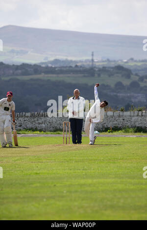 Cricket bowler in a village cricket match passing the umpire and about to deliver a ball at Kirkheaton in West Yorkshire, England - Stock Photo