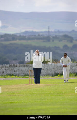 Umpire officiating in a village cricket match on a Saturday afternoon in summer in West Yorkshire, England - Stock Photo