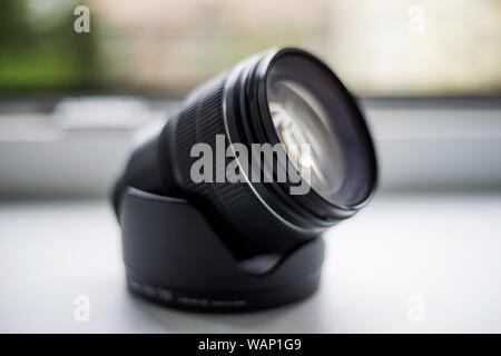 Camera lens sitting on lens hood on white background, no brand - Stock Photo