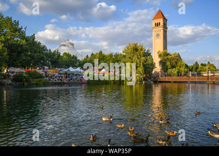 Festival goers enjoy the annual Pig out in the Park under the clock tower at Riverfront Park, as ducks swim in the Spokane River in Spokane Washington - Stock Photo