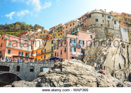 A young couple relaxes on the rocks above the swimming harbor and under the colorful town at the Cinque Terre village of Manarola, Italy - Stock Photo