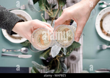 Top view of people eating and toasting with glasses of white wine. Friends or family different ages enjoying dinner. Table served for Christmas dinner - Stock Photo