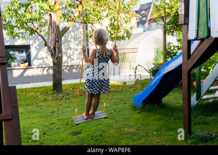 3-5 year old blond girl having fun on a swing outdoor. Summer playground. Girl swinging high. Young child on swing in garden - Stock Photo